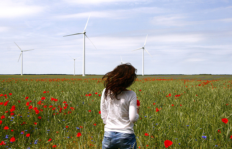 Woman in field with wind turbines